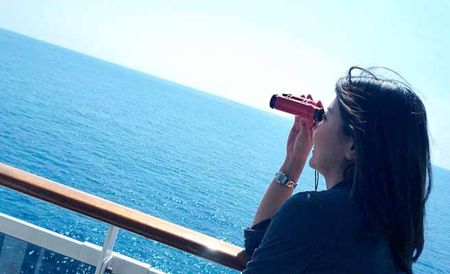 双眼鏡で海を見る女性