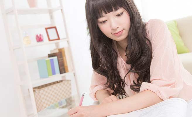 部屋で一人で勉強する女性