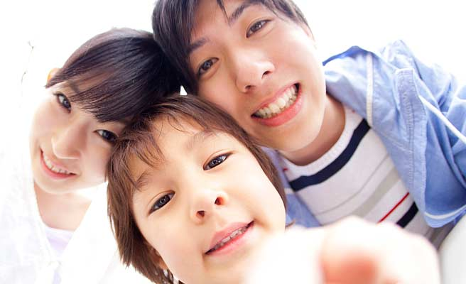 子供と両親が頭をつけて記念撮影