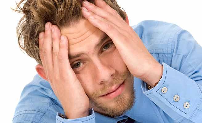 顔を両手で覆って困った表情の男性