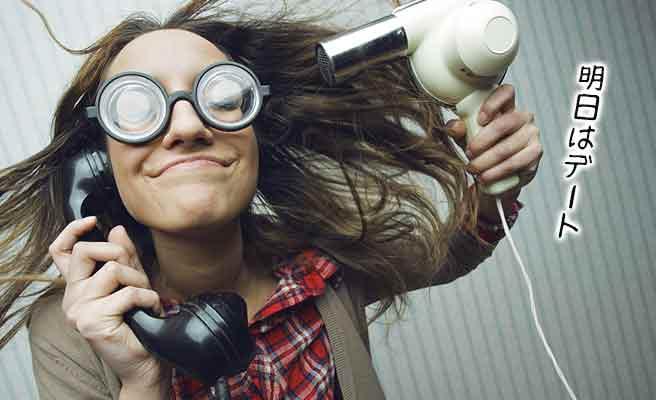 電話しながらヘアードライヤーをあてる女性