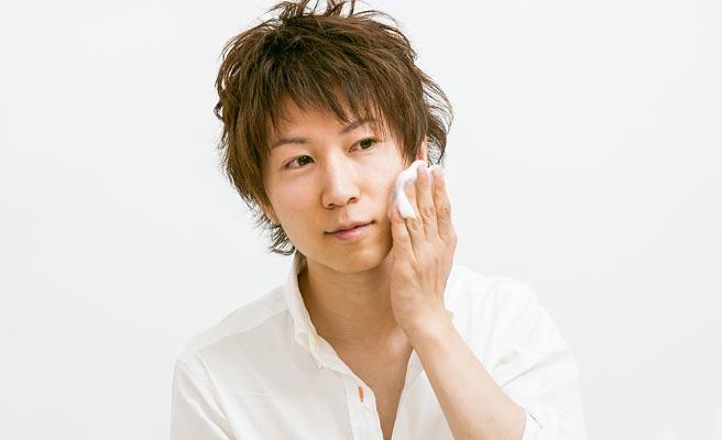 化粧水で顔の手入れをする男性