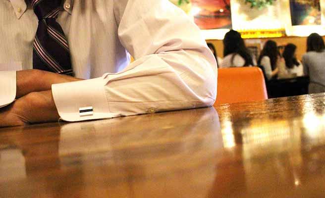 食堂の机に肘をつくサラリーマン
