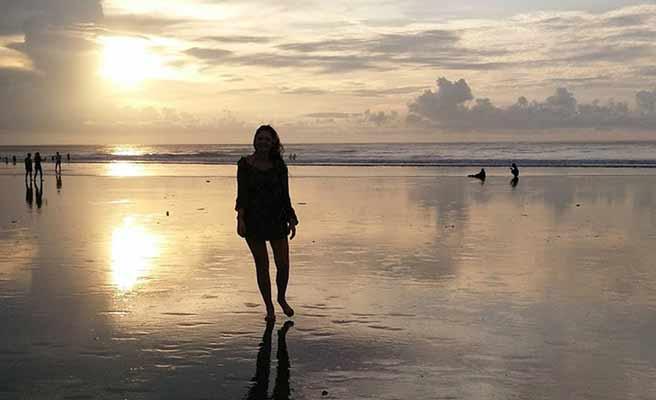 バリ島の砂浜を歩く女性