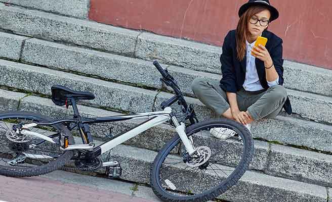 自転車の傍でスマホを見るオタク女性