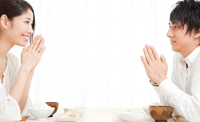 夫婦が向い合って朝食の挨拶