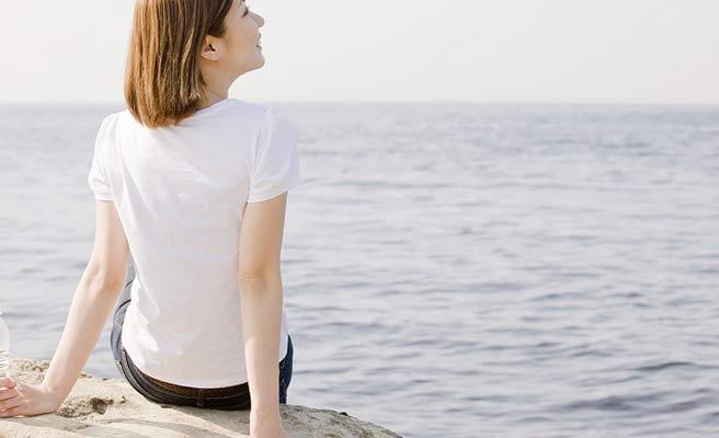 一人で海に向かう女性