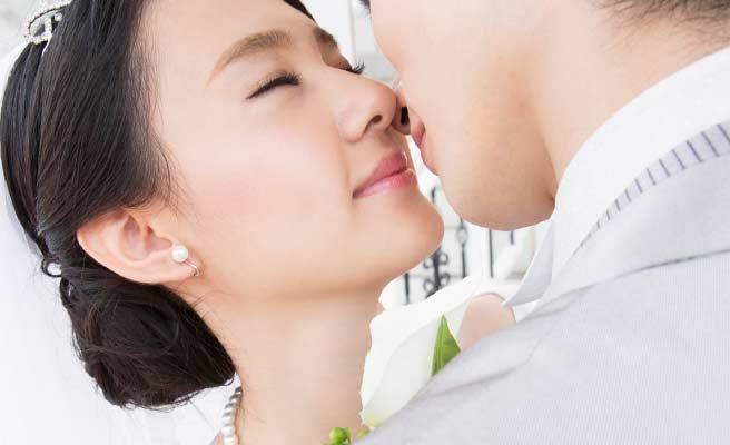 目を閉じて新郎とキスする新婦