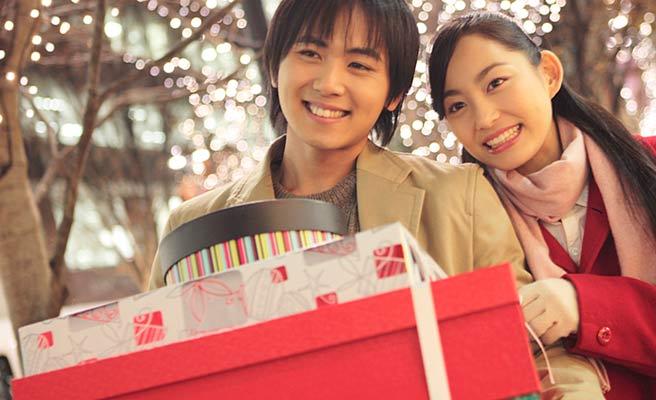 沢山のプレゼントを抱えた男性と傍に立つ女性