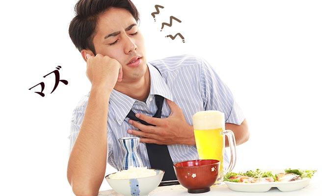 食事しながら「まずい」と胸を抑える男性