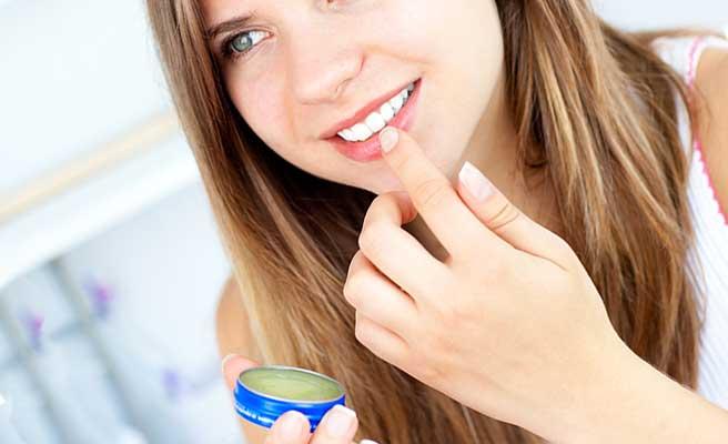 唇にクリームを塗る女性