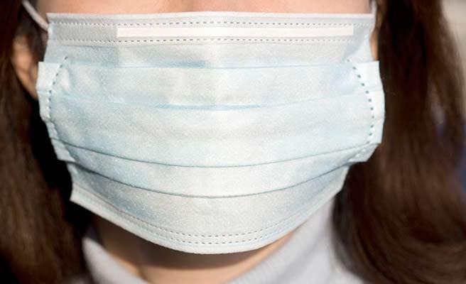 大き目のマスクで顔を覆う女性