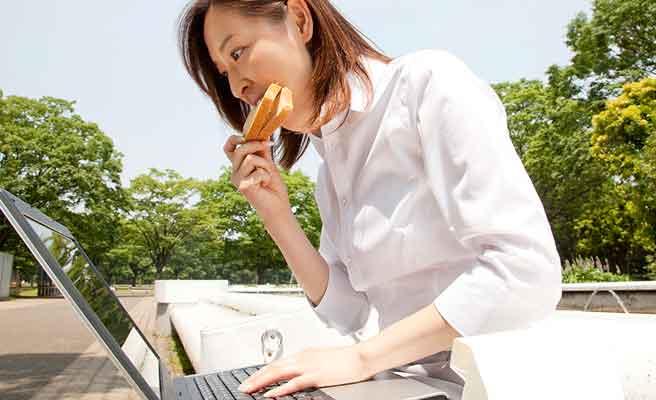 公園のベンチで昼食をとりながら仕事する女性