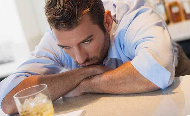 お酒を飲みながら考え込む男性