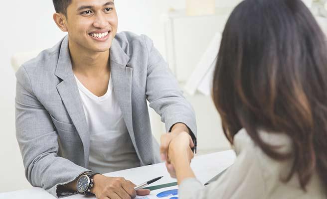 職場で女性と握手する男性