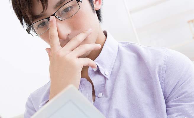 眼鏡を押さえながらノートを読むインテリ男性