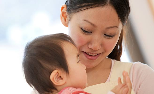 赤ちゃんを抱く保育士