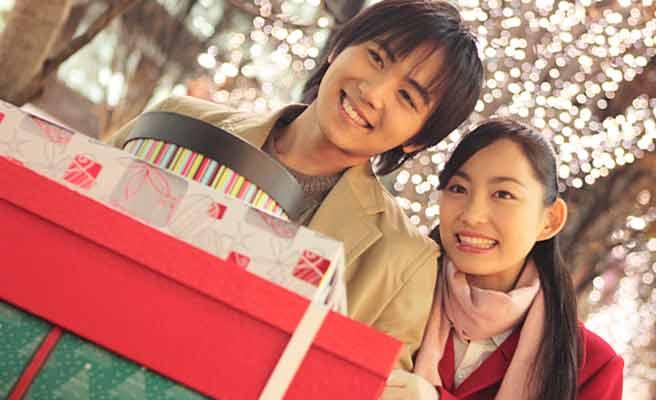 買い物した箱を重ねて持ち歩くカップル