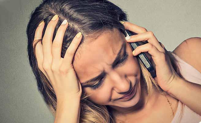 スマホを耳に当てながら哀し気な顔の女性