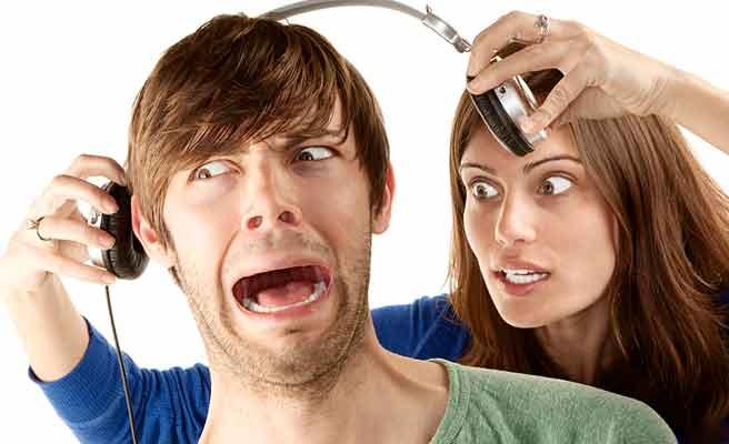 彼氏のヘッドホンを外して怒りの表情の女性