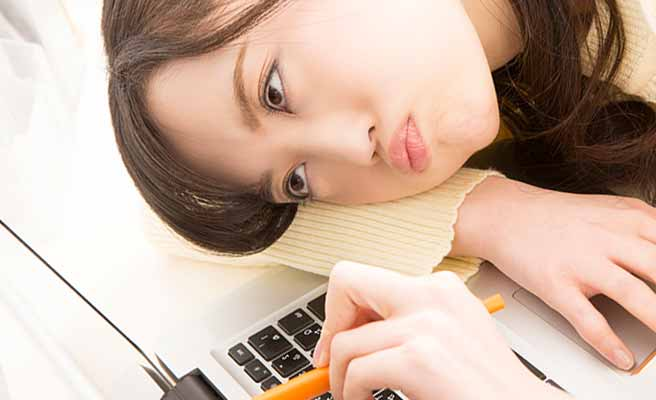 机にもたれて鉛筆の先を見つめる女性
