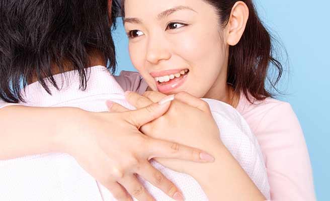 彼氏に抱き着いて肩越しに微笑む女性