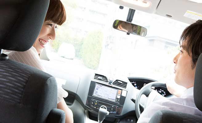 車内で笑顔で会話するカップル