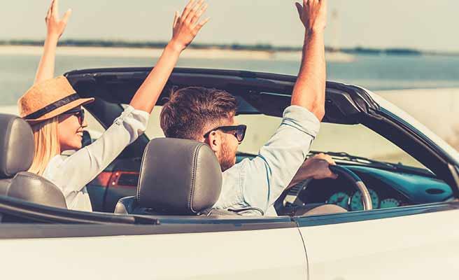 車の中から外に手を挙げて挨拶するカップル