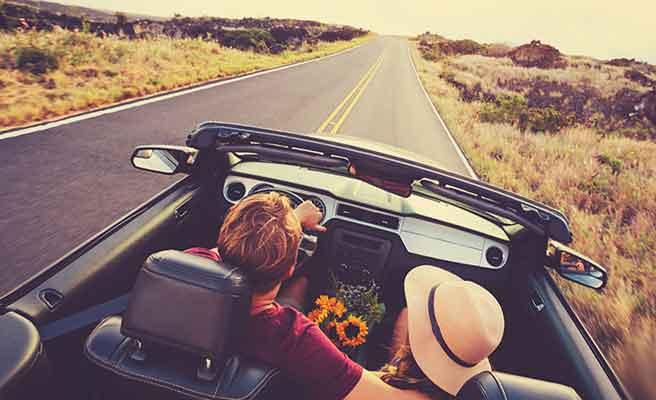 田舎道をドライブするカップル