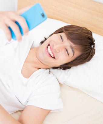 寝床でスマホを見る男性
