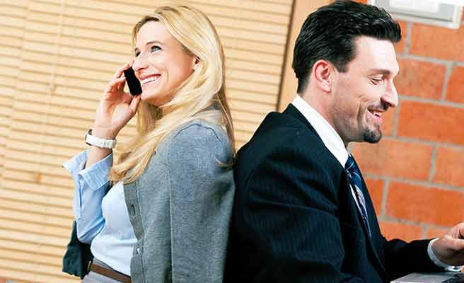 男性と背中に合わせに座り電話する女性