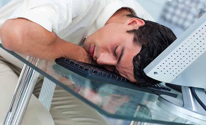 パソコンの前で眠る男性
