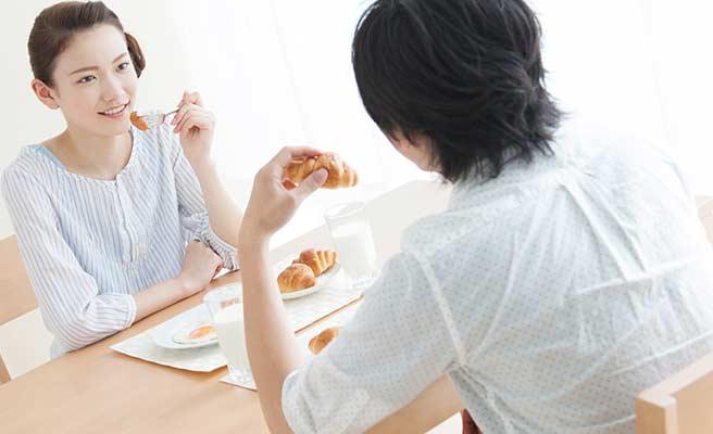 向い合って朝食をとる夫婦