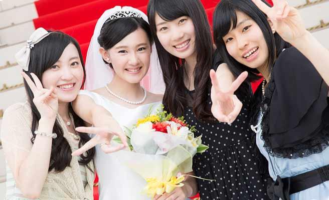 結婚式で新婦と一緒に写真をとる女友達