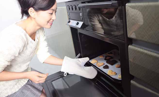 オーブンでお菓子を焼く女性