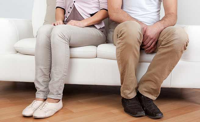 違う方に体を向けてソファに並んで座るカップル