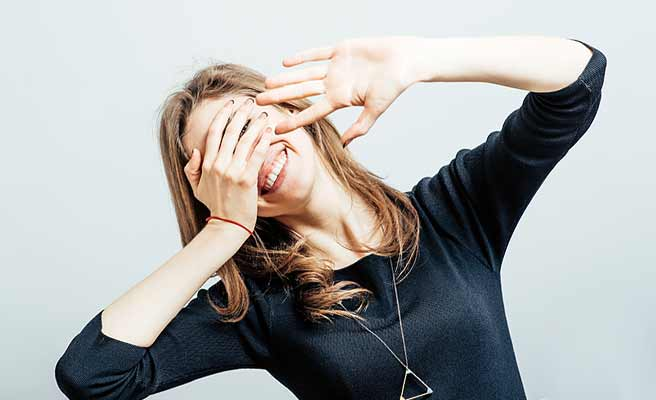 顔を手で隠す女性