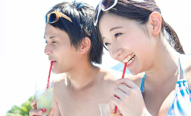 トロピカルジュースを飲む水着のカップル