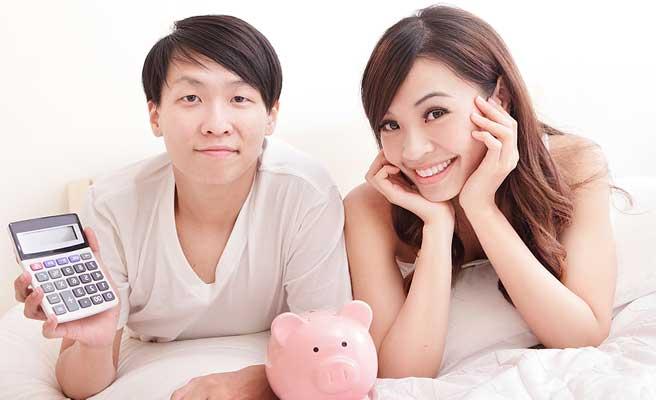 貯金箱と計算機で相談するカップル