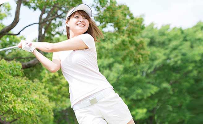 ゴルフクラブを振る女性