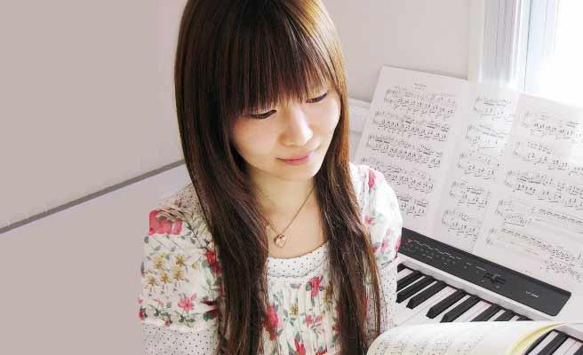 ピアノの前で楽譜を見る女性