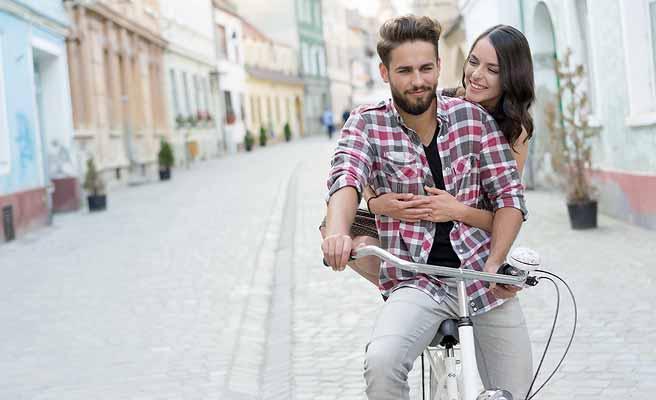彼氏の自転車の後ろに乗って笑顔の女性