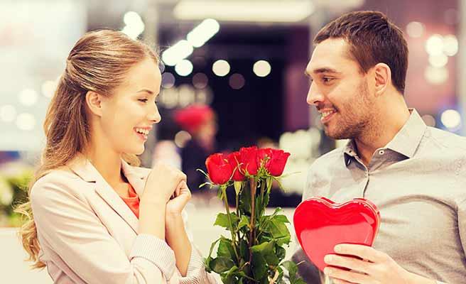 彼氏の持つハートのプレゼントに笑顔の女性