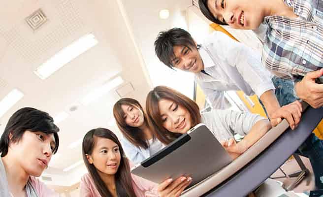 パソコンを見る女学生の周りに集まる学生たち