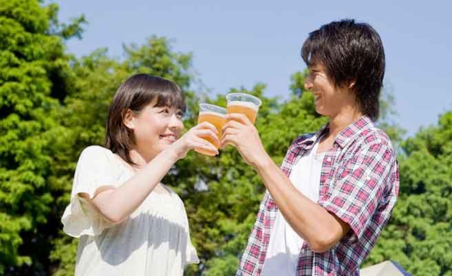 戸外でビールを飲む男女
