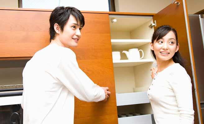 夫婦が台所の収納扉を開いて確認している