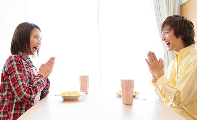 向かいあって食事の挨拶をするカップル