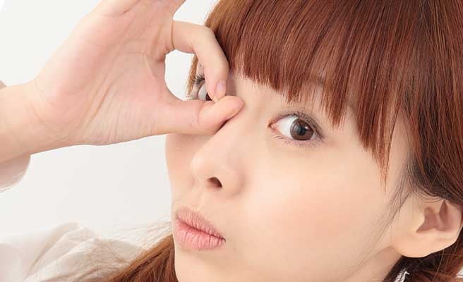 手で目の上に丸を作る女性