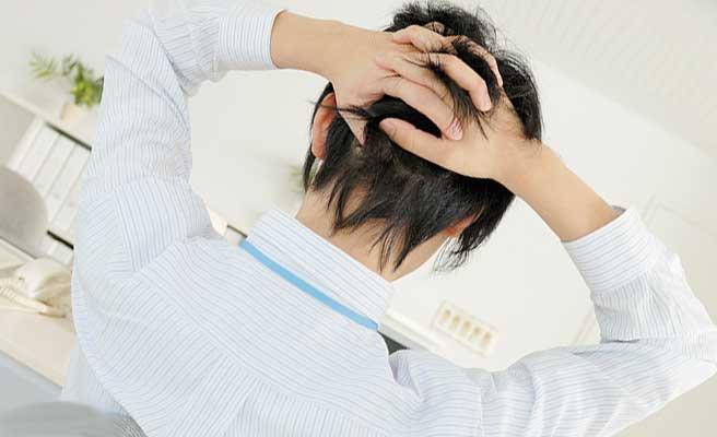 職場で頭を抱える男性