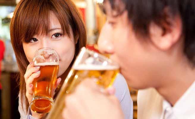 飲み屋で男性とお酒に付き合う女性